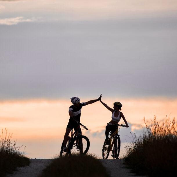 sporty woman man riding bicycles having fun outside silhouettes sportsmen highing five posing road sunset time non urban scene